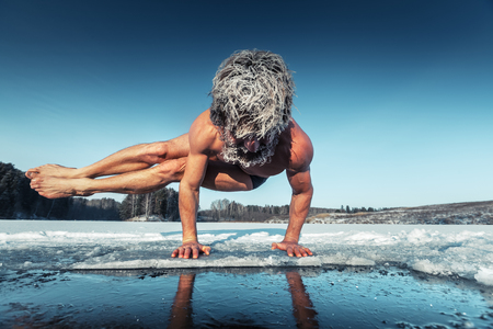 frozen lake: Man doing yoga exercise (parsva bakasana) on the ice of frozen lake