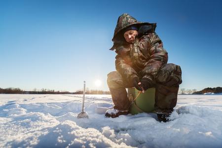 pecheur: Pêcheur sur un lac à l'hiver journée ensoleillée