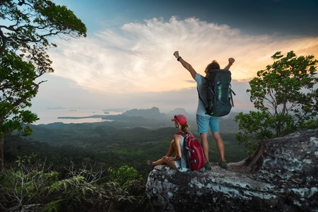 top mountain: Two hikers relaxing on top of the mountain and enjoying sunset valley view