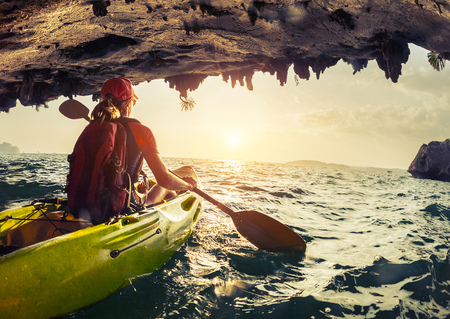cave exploring: Lady paddling the kayak in the rough sea at sunset.