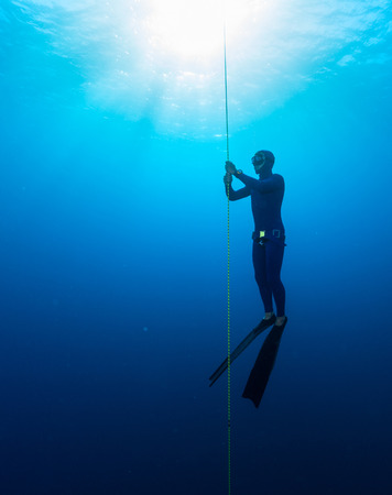 free diving: Free diver performing warm up dive - static apnea on the depth Stock Photo