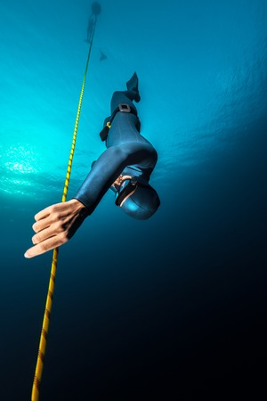 free diving: Lady freediver descending along the rope. Free immersion discipline