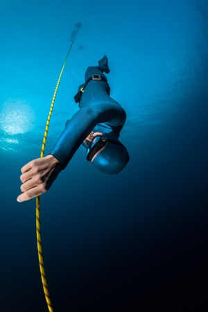 immersion: Lady freediver descending along the rope. Free immersion discipline