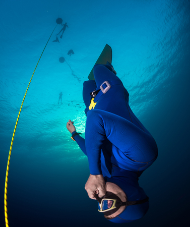 immersion: Freediver descending along the rope with monofin. Free immersion discipline