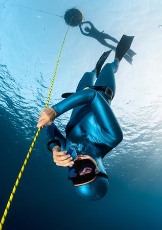 picada: Señora buceador desciende a lo largo de la cuerda a su compañero de observación en la superficie de la boya. La disciplina de inmersión libre Foto de archivo