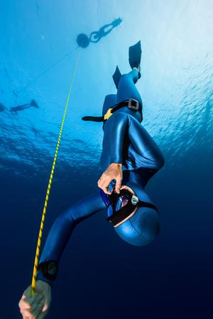Señora del freediver descendente a lo largo de la cuerda. la disciplina de inmersión libre