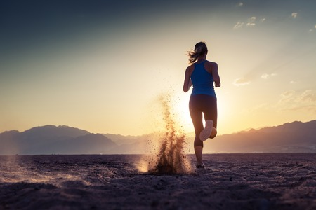 sport: Lady running in the desert at sunset