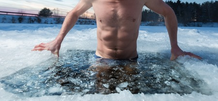 Young man bathing in the ice hole. Focus on the ice in a water only 스톡 콘텐츠