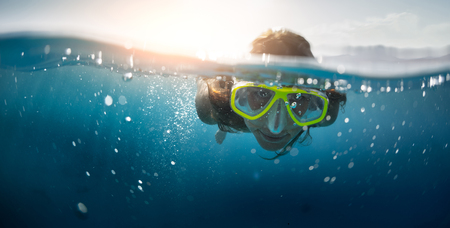 beneath the surface: Close up split shot of the young lady snorkeling in the clear tropical sea