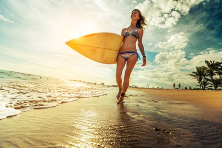 surf board: Lady walking with surfboard along the tropical beach Stock Photo