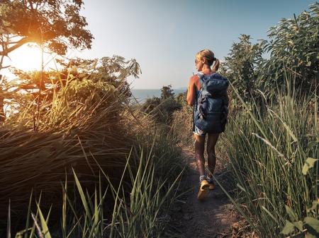 buisson: Randonneur avec sac à dos marchant dans la prairie avec de l'herbe luxuriante au jour ensoleillé chaud Banque d'images