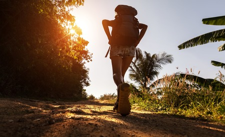 Caminante con mochila caminando sobre el camino de tierra en el día caluroso y soleado Foto de archivo