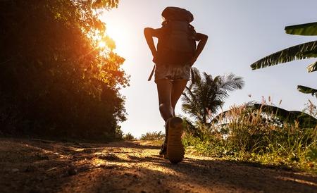 MOCHILA: Caminante con mochila caminando sobre el camino de tierra en el día caluroso y soleado Foto de archivo