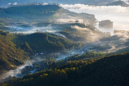 adams: Morning fog in the valley with lake and villages. View from the mountain of Adams Peak, Sri Lanka Stock Photo