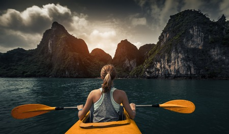 outdoor sport: Woman exploring calm tropical bay with limestone mountains by kayak. Ha Long Bay, Vietnam
