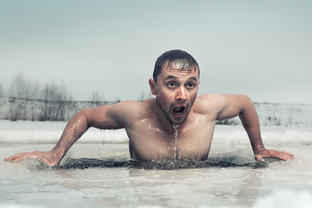 plunge: Man swimming in the ice hole with emotional face
