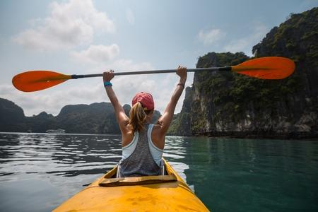 vietnam: Woman exploring calm tropical bay with limestone mountains by kayak. Ha Long Bay, Vietnam