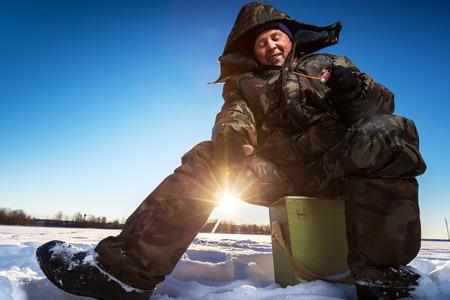 full of holes: Mature man fishing on the winter lake