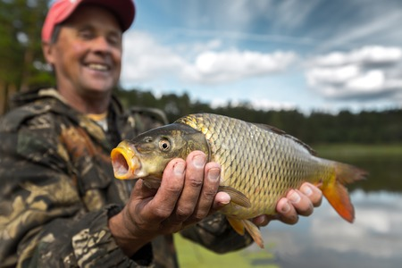 cyprinidae: Happy smiling fisherman holding his trophy carp (Cyprinus carpio) with lake on the background. Focus on the fish