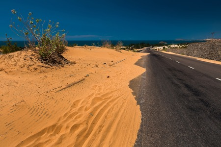 ne: Asphalt road with sandy dunes. Mui Ne town area, Vietnam