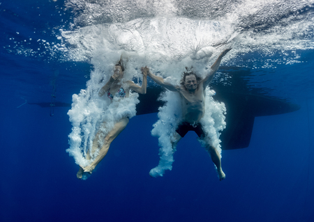 bottomless: Underwater view of the young couple having fun and jumping into the clear sea from a boat
