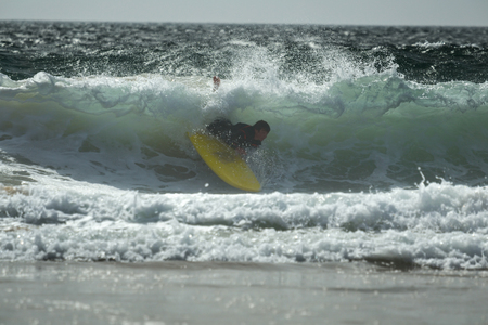 close out: Beginner surfer wiping out on the wave