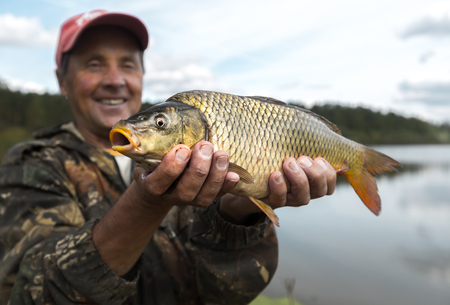 cyprinidae: Happy smiling fisherman holding his carp (Cyprinus carpio) with lake on the background. Focus on the fish