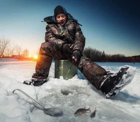 ice fishing: Mature man fishing on the winter lake