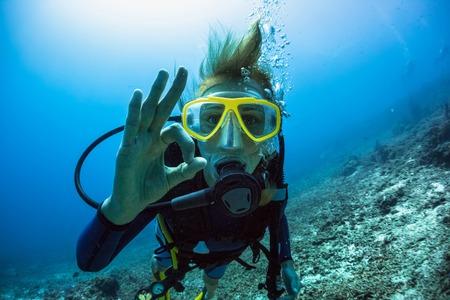 [Ok] を示す女性スキューバダイバー水中信号します。