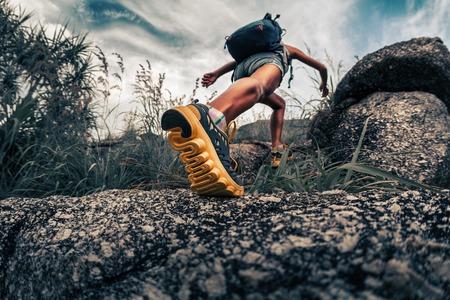 Lady escursionista a piedi attraverso la terra rocciosa. Focus sul piede Archivio Fotografico