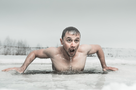 Man zwemmen in het ijs gat met emotionele gezicht Stockfoto