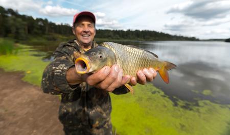 hombres maduros: pescador sonriente feliz que detiene a su carpa (Cyprinus carpio) con el lago en el fondo. Centrarse en los peces