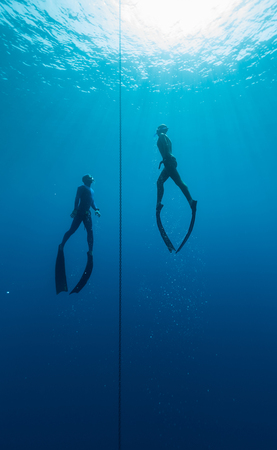 free diving: Two free divers training in the open sea