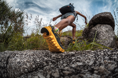 edge: Lady hiker walking through the rocky land. Focus on the foot Stock Photo