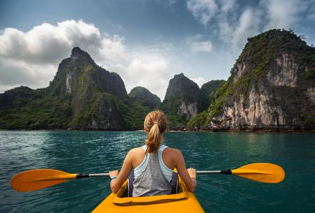piragua: Exploración de la mujer tranquila bahía tropical con montañas de piedra caliza en kayak. Ha Long Bay, Vietnam Foto de archivo