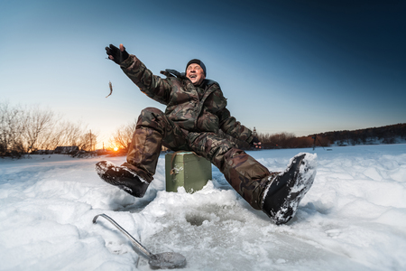 ice fishing: Happy fisherman with tiny fish on the winter lake Stock Photo