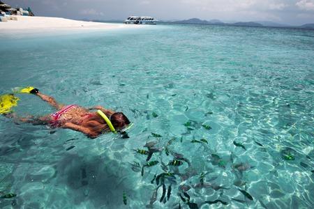 Jeune snorkeling dame avec du poisson dans une mer bleue claire