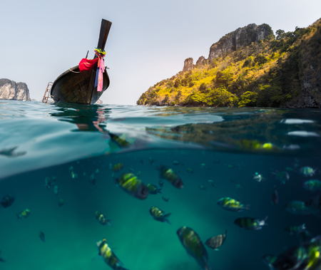 long tail: Split shot with fish underwater and long tail boat on the surface. Focus on the boat only Stock Photo
