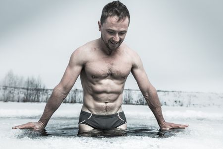Young man having recreational swim in the ice hole Stock Photo