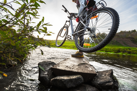 off road biking: Lady with bicycle crossing the river Stock Photo