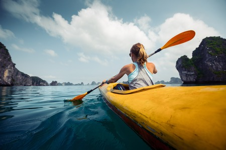 Woman exploring calm tropical bay with limestone mountains by kayak. Ha Long Bay, Vietnam