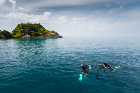 submerging: Divers start submerging underwater on the tropical dive site