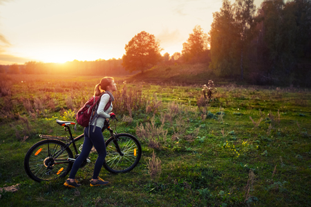 off road biking: Lady walking with bicycle on the green autumn meadow at sunset Stock Photo