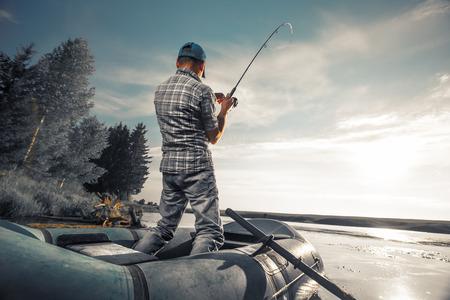 bateau de pêche: homme qui pêche d'âge mûr sur le lac de bateau pneumatique