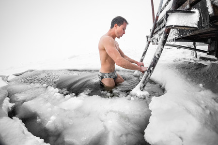 겨울 호수에서 얼음 구멍에서 수영하는 젊은 남자 스톡 콘텐츠