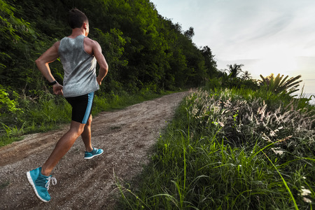 wet t shirt: Man jogging on the gravel road at sunset Stock Photo