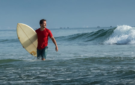 short wave: Happy surfer with short board walking from the ocean