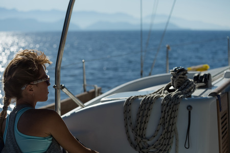 sail: Young woman relaxing on the sail boat Stock Photo