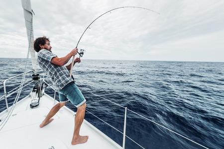 Young man fishing hard in open sea from sail boat Stockfoto
