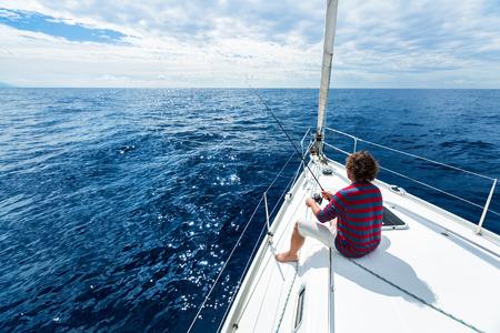 Man Angeln in einem ruhigen See von einem Segelboot Standard-Bild - 53541510
